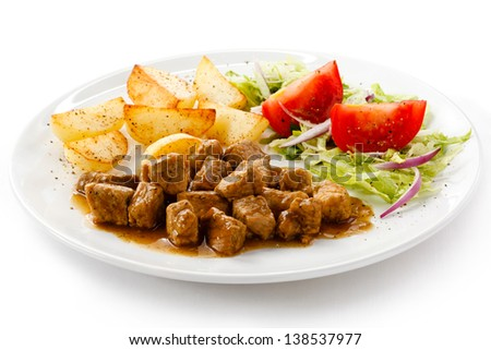 Goulash with baked potatoes and vegetables - stock photo