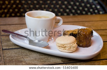 Gourmand coffee in a Parisian cafe. Served with traditional French sweets - macaroon cookie, eclair pastry and canele - stock photo