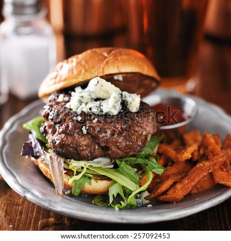 gourmet burger with blue cheese and sweet potato fries on metal plate.  - stock photo
