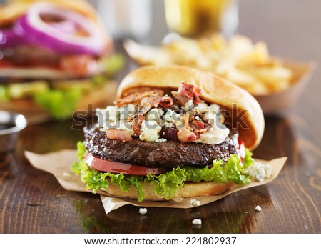 gourmet burgers on wooden table with bleu cheese and bacon - stock photo