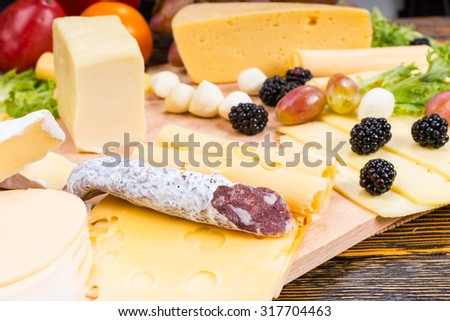 Gourmet Cheese Board Featuring Variety of Cheeses, Cured Meat Sausage and Fresh Fruit Served on Rustic Wooden Table with Wood Grain - stock photo