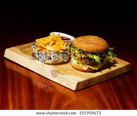 gourmet cheeseburger served open faced with selective focus on burger - stock photo