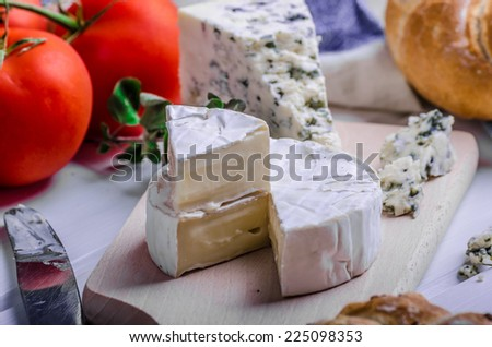 Gourmet cheeses - camembert and blue cheese on a cutting board, homemade pastries - stock photo