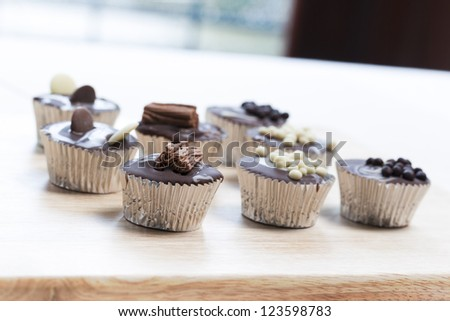 Gourmet chocolate cupcakes in silver cupcake wrappers - stock photo