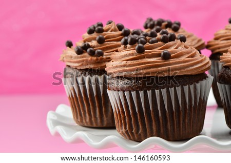 Gourmet chocolate cupcakes with chocolate chiffon icing and chocolate balls on white cake stand with a deep pink background - stock photo