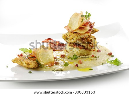 gourmet fish dish, turbot fillets flavored crust, chips, rosti, creamed potatoes, crispy bacon on white square plate - stock photo