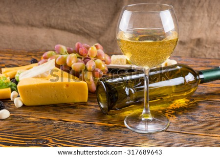 Gourmet Food Still Life - Glass of White Wine on Rustic Wooden Table with Fallen Bottle and Variety of Cheeses and Grapes - stock photo