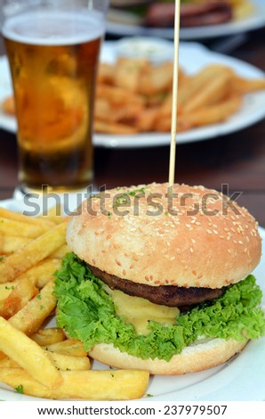 Gourmet hamburger and fries with mug of beer in background - stock photo