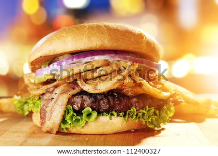 Gourmet hamburger with fried onion straws and cityscape background. - stock photo