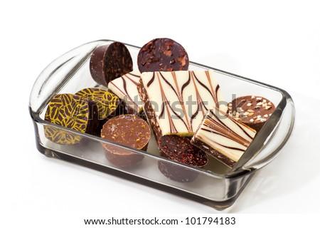 gourmet handmade chocolates in glass tray on white background - stock photo