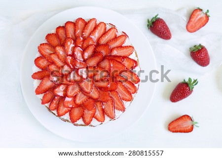 Gourmet homemade party strawberry sponge cake with whipped cream and fresh strawberries on white kitchen table background. Top view. Rustic style and natural light - stock photo