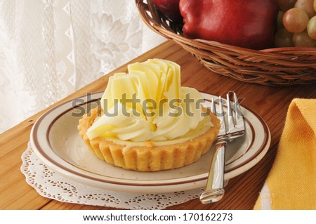 Gourmet key lime dessert tart with a basket of fruit - stock photo