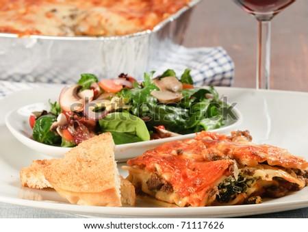 Gourmet Lasagna with chef salad and garlic toast - stock photo