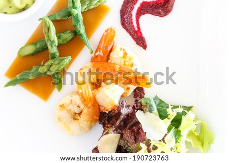 Gourmet meal of grilled shrimp with succulent fresh green asparagus tips and salad, close up view from above - stock photo