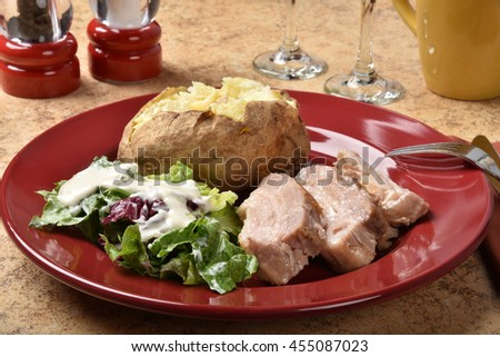 Gourmet pork belly dinner with salad and baked potato - stock photo