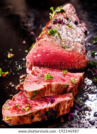 Gourmet portion of rare roast beef fillet garnished with chopped fresh herbs carved ready for serving for a delicious dinner - stock photo