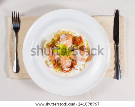 Gourmet salmon seafood starter with bite sized portions of fish drizzled with a cream sauce and seasoned with herbs, overhead view on a white plate - stock photo