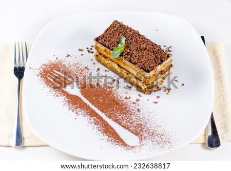 Gourmet Slice of Delicious Chocolate Cake Dessert with Choco Shavings, Prepared on White Plate with Fork Outline Using Cocoa Powder. Served on White Table with Napkin and Utensils. - stock photo