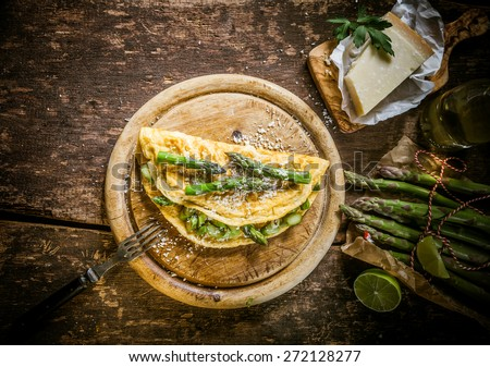 Gourmet Tasty Egg Omelette with Asparagus and Cheese on Top of Wooden Round Cutting Board, Served on Rustic Wooden Table, Captured in High Angle View. - stock photo