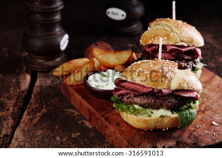 Gourmet Tasty Steak Burgers with Ham Slices on a Wooden Tray with Potato Wedges and Dipping Sauce. - stock photo