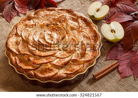 Gourmet traditional holiday apple pie sweet baked dessert food with cinnamon and apples on vintage background. Autumn decor. Rustic style and natural light. - stock photo