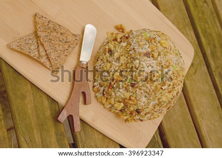 Gourmet Vegan Cheese Ball with a Cheese Spreader for a festive party appetizer on rustic table - stock photo
