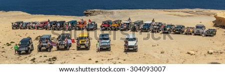 GOZO, MALTA - AUGUST 2, 2015: Land Rover owners from Malta gather for a trip to Gozo on the occasion of International Land Rover Day 2015.  The iconic Defender goes out of production in December 2015. - stock photo