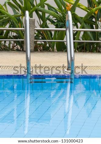 Grab bars ladder in swimming pool - stock photo