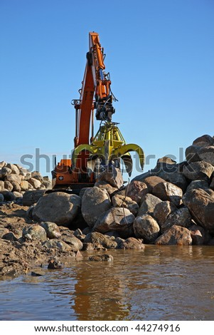 Grab dredger moving rocks for a coast protection project. - stock photo