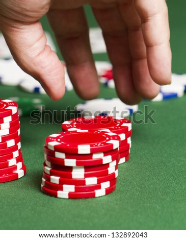 Grab Poker Chips a close up as a hand moves in to grab some red poker chips on a poker table. - stock photo