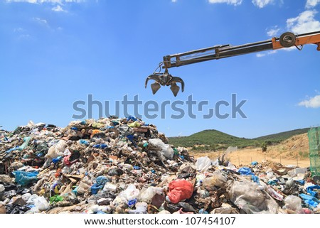 Grabber crane working in landfill - stock photo