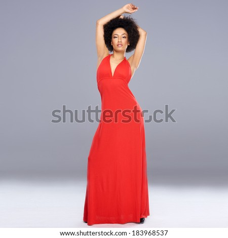 Graceful beautiful young African American woman in a r long ed gown standing with her arms raised above her head against a grey background with copyspace - stock photo