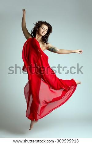 Graceful female dancer posing in jump - stock photo
