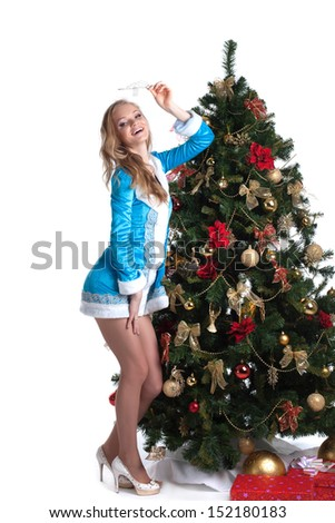 Graceful Snow Maiden posing with decorated fir - stock photo