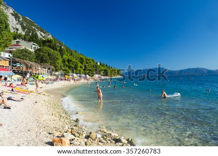 Gradac, Croatia-August 18, 2014: Tourists on the beach in Gradac with mountains and Peljesac peninsula on the background, Croatia - stock photo