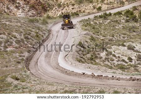 Grader working on dirt road in Arizona - stock photo