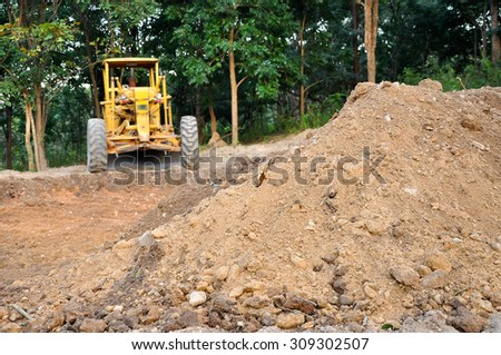 Graders are commonly used in the construction and maintenance of dirt roads and gravel roads. - stock photo