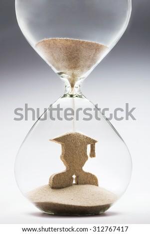 Graduate figure made out of falling sand inside hourglass - stock photo
