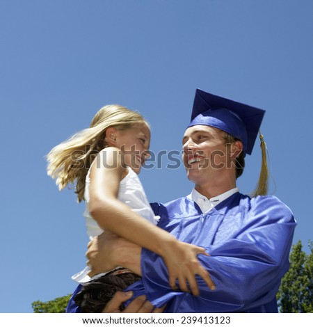 Graduate Holding His Little Sister - stock photo