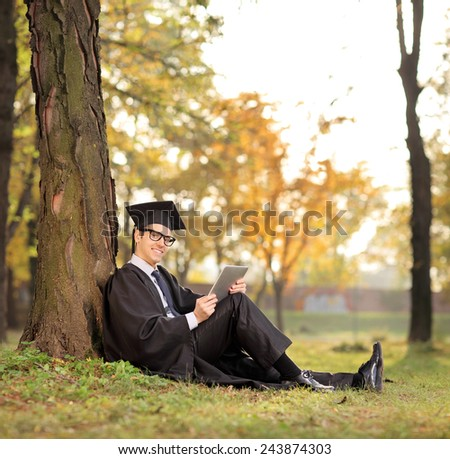 Graduate student holding a tablet in park and looking at the camera seated on the grass shot with tilt and shift lens - stock photo