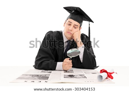 Graduate student searching for job in the papers isolated on white background. The newspaper is custom made, text is Latin and the pictures are my copyright. Additionally property release uploaded. - stock photo