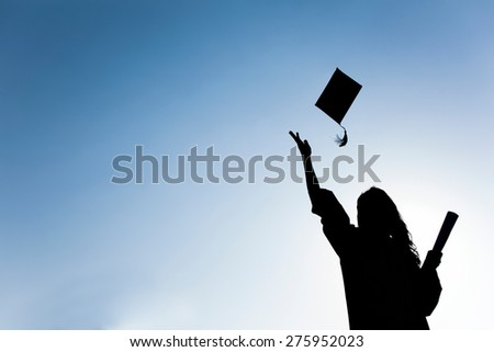 Graduate students tossing up hats over blue sky - stock photo