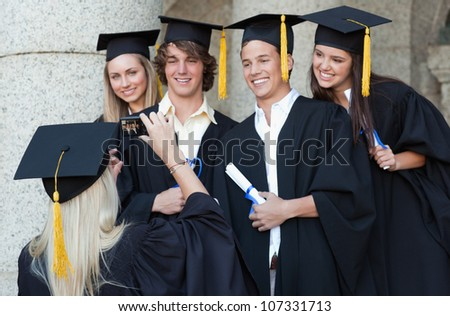 Graduate taking a picture of her friend in front of the university - stock photo