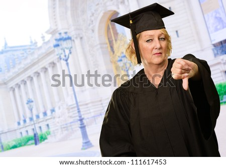 Graduate Woman Showing Thumb Up Down, Outdoors - stock photo