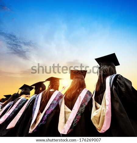 Graduates face the morning sun - stock photo