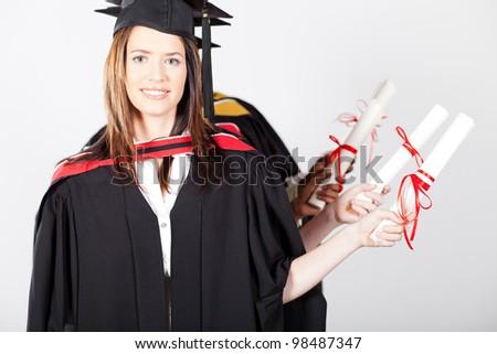 graduates holding diploma at graduation - stock photo