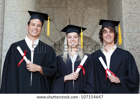 Graduates holding their diploma while posing with university in background - stock photo
