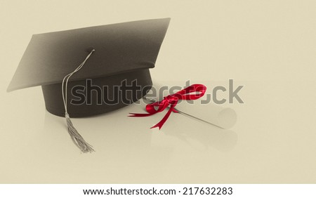 Graduation cap and diploma. Old Scroll paper - stock photo