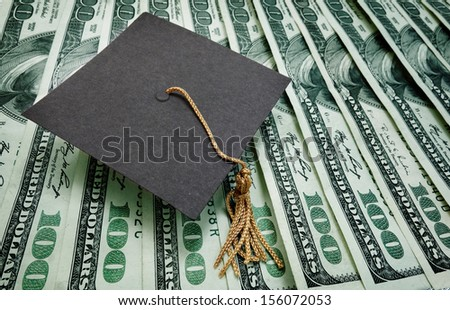 graduation cap on assorted hundred dollar bills - education concept                                - stock photo