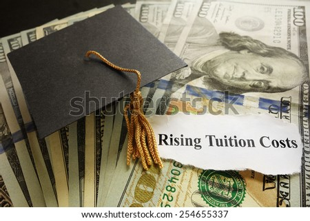 Graduation cap on cash with Rising Tuition Costs newspaper headline - stock photo